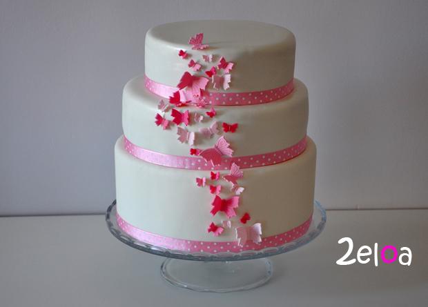 Tarta de fondant de comunión blanca y rosa con mariposas